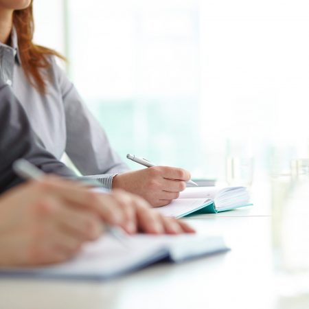 Hand of businesswoman with ballpoint over open notebook at convention